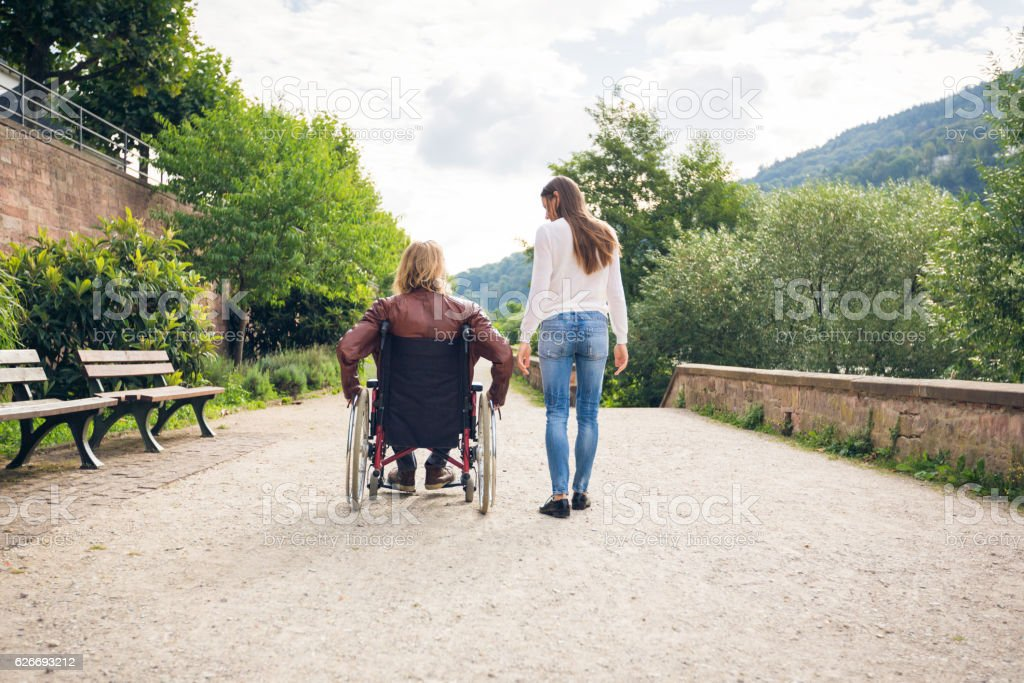 Young couple in wheelchair strolling in the park - foto de stock