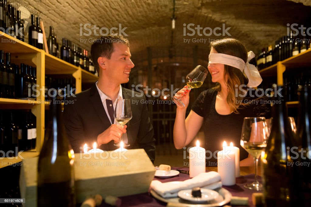 Young Couple In Wine CellarTasting Wine Blindfold stock photo