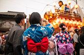祭りのパレードの写真を撮る浴衣の若いカップル