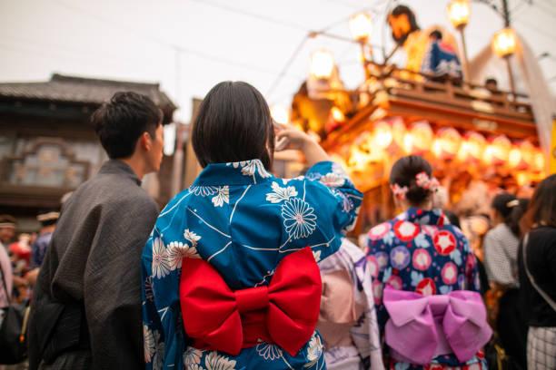 祭りのパレードの写真を撮る浴衣の若いカップル - 伝統的な祭り ストックフォトと画像