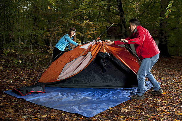 royalty free woman and man putting up a tent pictures images and