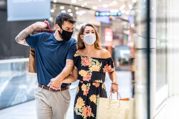 A young couple is carrying shopping bags with masks on their faces and walks, shopping during a pandemic stock photo