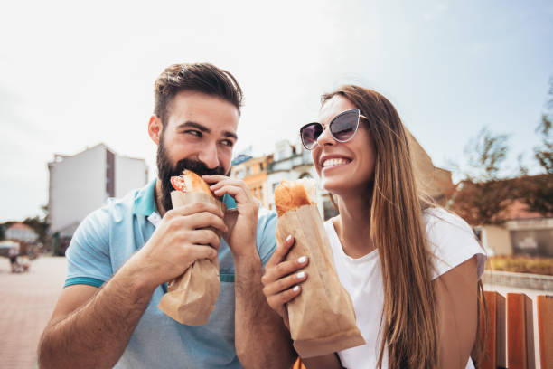 Young couple is eating sandwiches and having a great time Young couple is eating sandwiches and having a great time female sandwich stock pictures, royalty-free photos & images