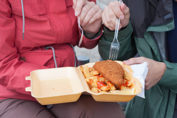 Young couple is eating traditional London food fish and chips stock photo