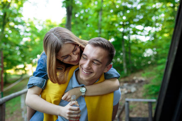 Young couple is enjoying their love in forest and smiling stock photo