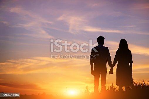 istock young couple is holding hands on a background sunset silhouette 850429336