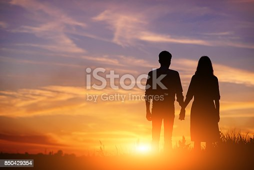 istock young couple is holding hands on a background sunset silhouette 850429354