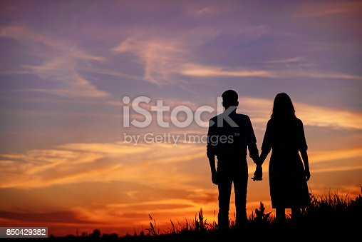 istock young couple is holding hands on a background sunset silhouette 850429382