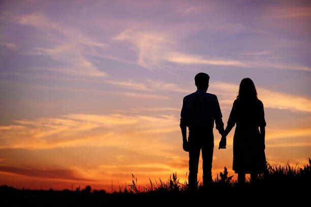 young couple is holding hands on a background sunset silhouette stock photo