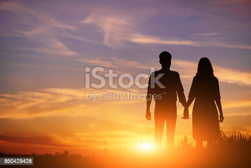 istock young couple is holding hands on a background sunset silhouette 850429428