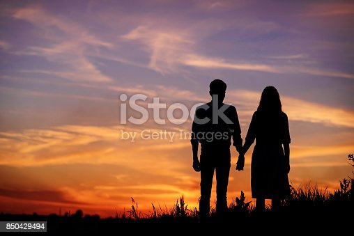 istock young couple is holding hands on a background sunset silhouette 850429494