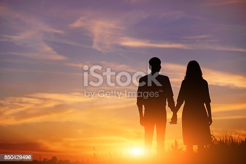istock young couple is holding hands on a background sunset silhouette 850429496