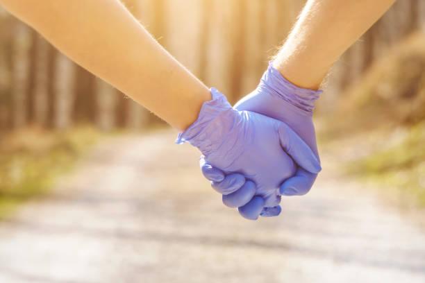Junges Paar hält Hände mit Schutzhandschuhen – Foto