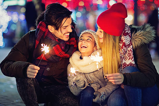Young couple is hugging their daughter at Xmas stock photo