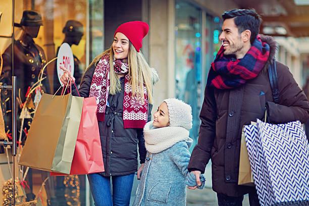 young couple is looking in the shop window at xmas - geschenke eltern weihnachten stock-fotos und bilder