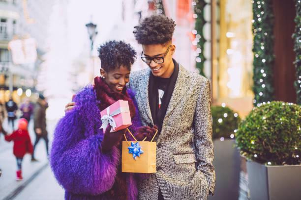 junges paar ist ein weihnachtsgeschenk öffnen. - schwarze romantik stock-fotos und bilder