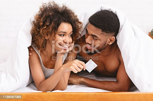 Safety sex concept. Male and female hands holding condom, closeup
