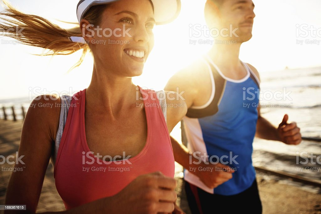 Young couple jogging along the beach royalty-free stock photo