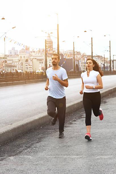 молодая пара, бег в стамбуле, galata bridge. - каракёй стамбул стоковые фото и изображения