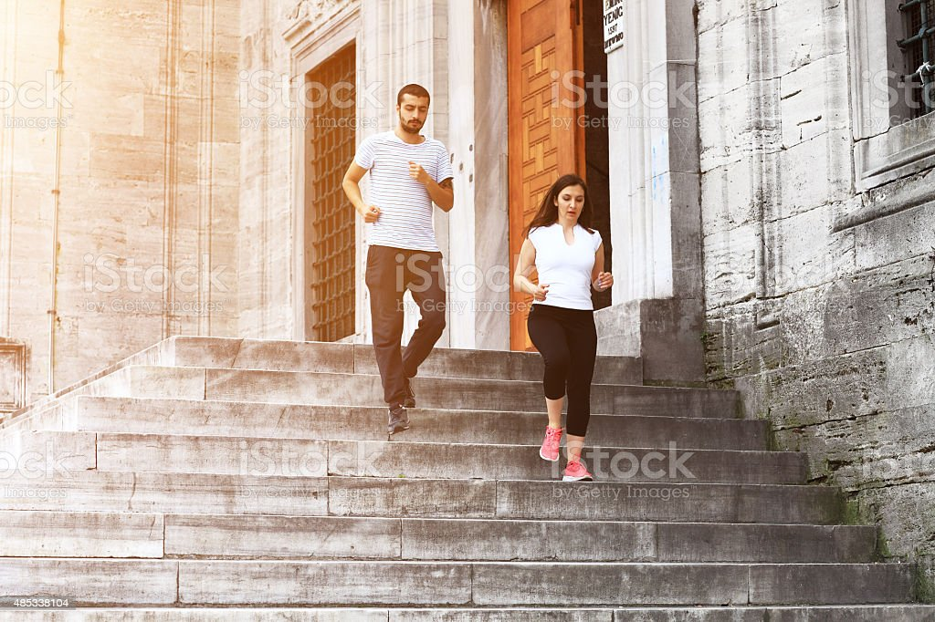 Young couple jogging in Istanbul, New Mosque stairs stock photo