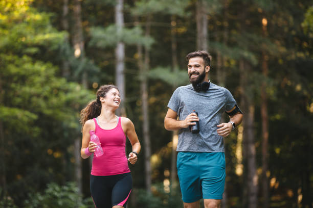 Young couple jogging in nature stock photo