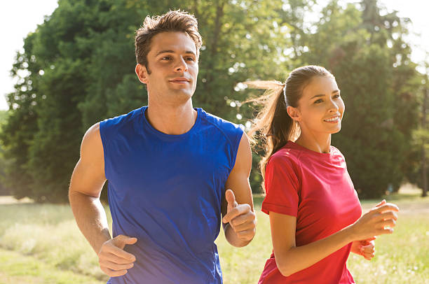 Young couple jogging together outdoors in sunshine stock photo