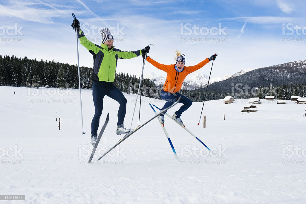 Young couple jumping after cross country skiing stock photo
