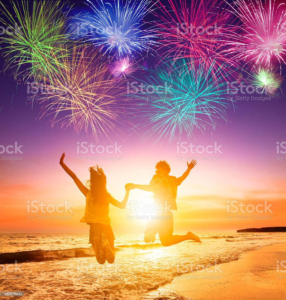 young couple jumping on the beach with fireworks background stock photo