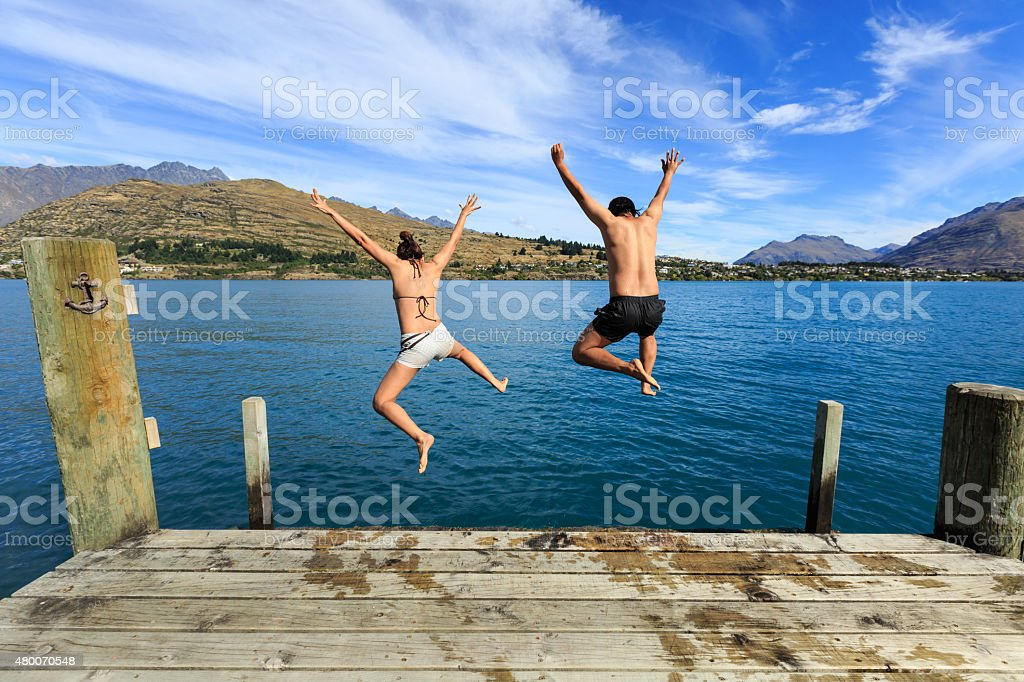 Young couple jumping to the lake stock photo