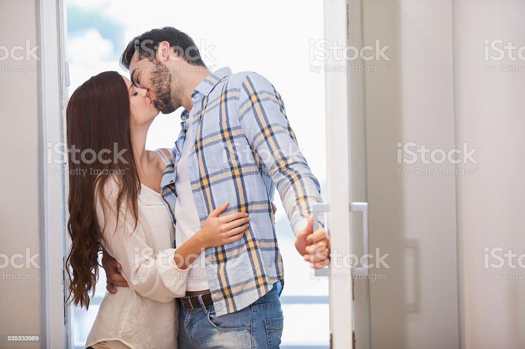 Pareja joven beso que abre la puerta frontal - foto de stock
