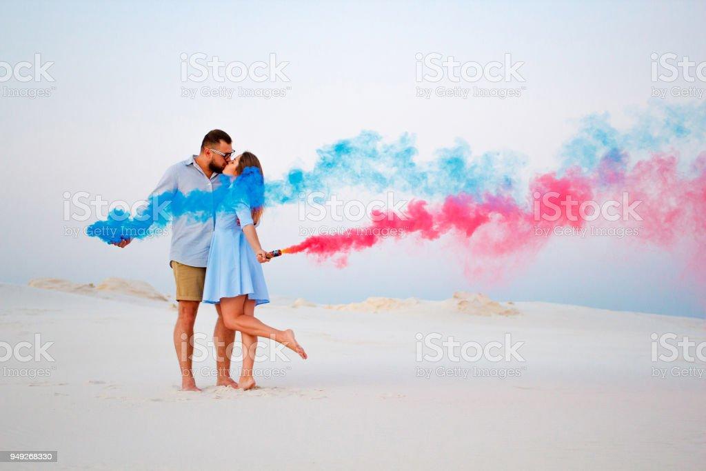 junges Paar küssen und mit farbigen Rauch in Händen, romantisch zu zweit mit blau und rot Rauchbombe am Strand – Foto