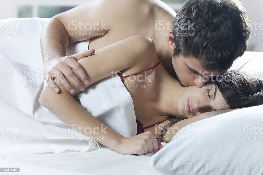 Young couple kissing and hugging on the bed in bedroom stock photo