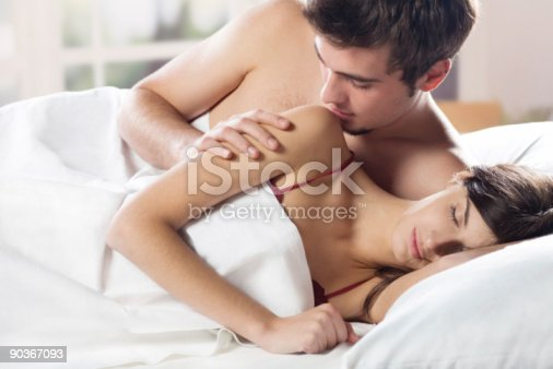888274920istockphoto Young couple kissing and hugging on the bed in bedroom 90367093