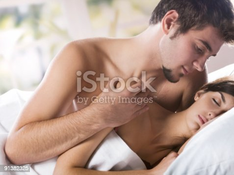 888274920 istock photo Young couple kissing and hugging on the bed in bedroom 91382325