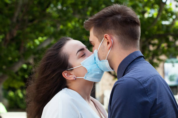 Young couple kissing and wearing protective face masks stock photo