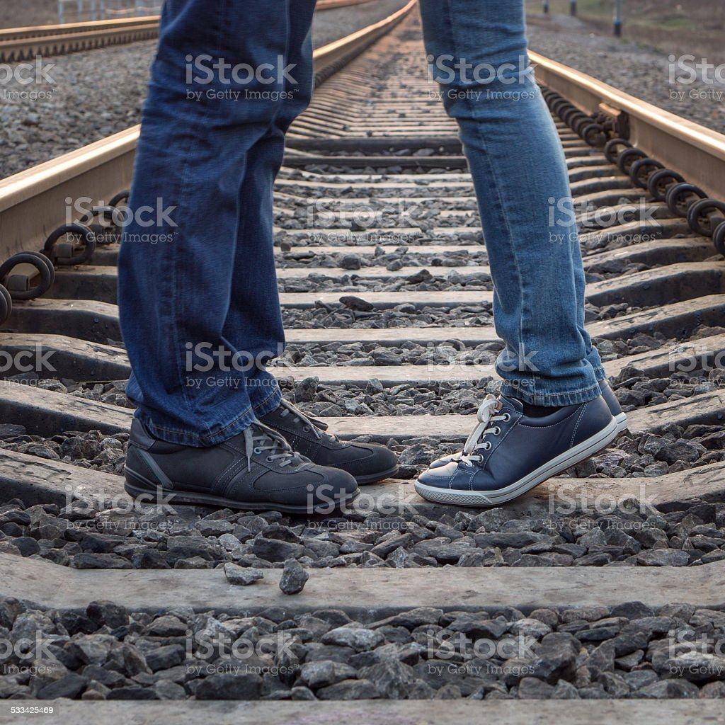 Young couple kissing at railways rails stock photo
