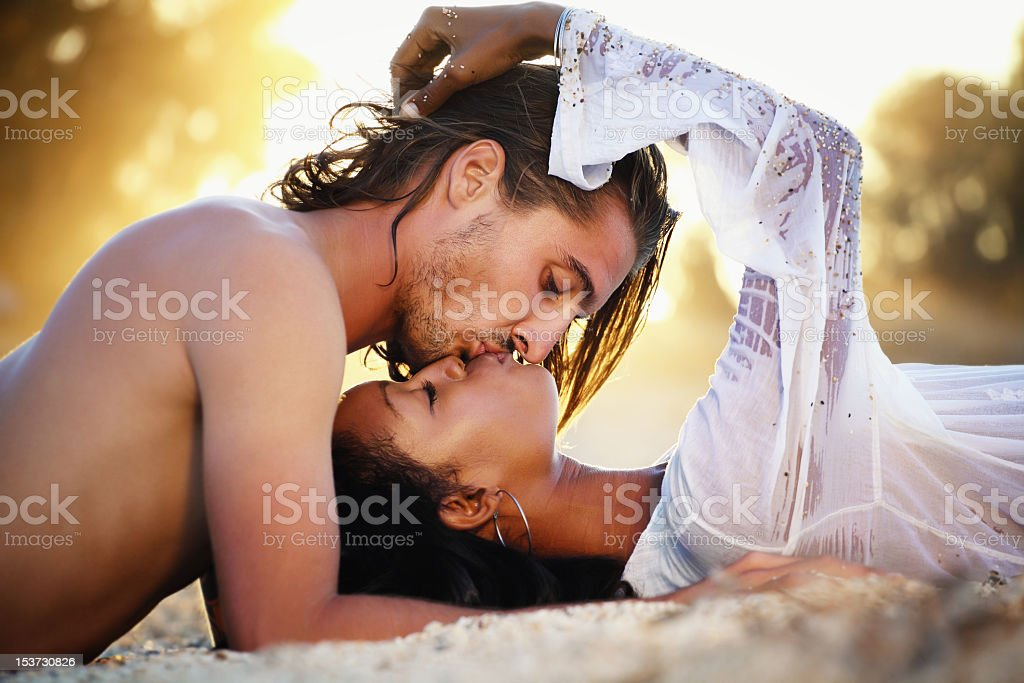 Young couple kissing at sunset stock photo
