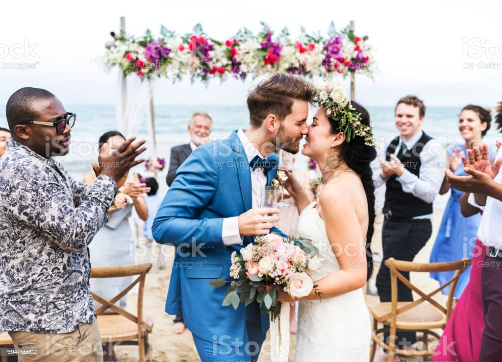 Young couple kissing at wedding reception stock photo