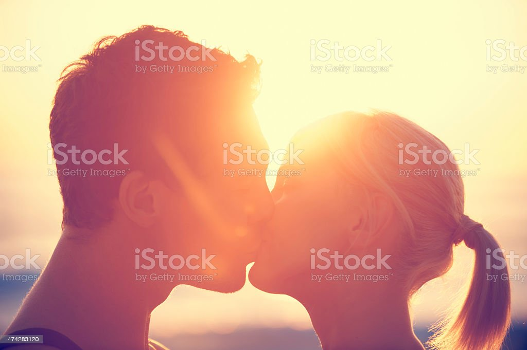 Young couple kissing each other at sunset. stock photo