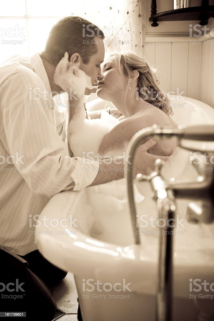 Young couple kissing in bathroom with vintage bathtub royalty-free stock photo