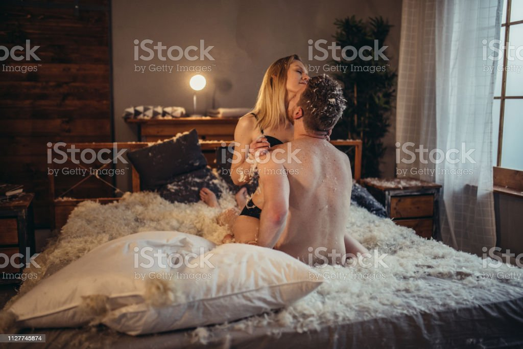 Man and woman, young heterosexual couple in bed, sitting in bed,...