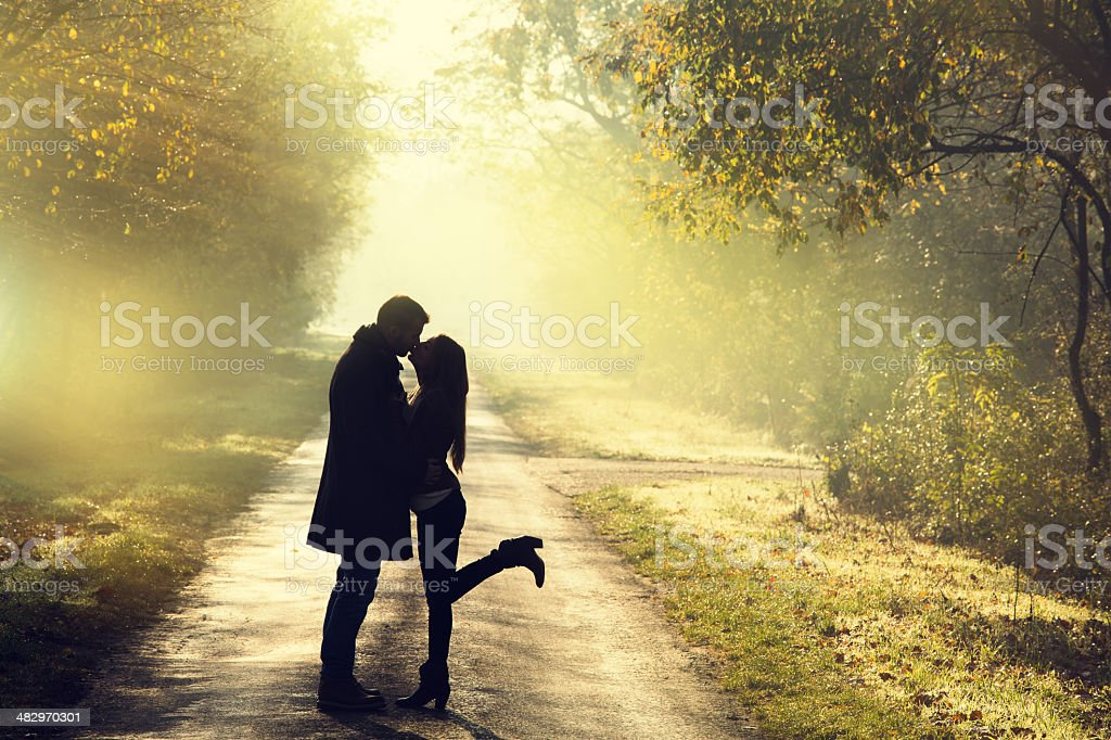 young couple kissing in the autumn sunshine stock photo