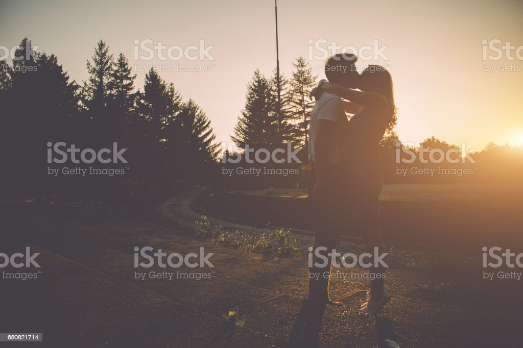 Young couple kissing on a beautiful summer day in the sunset stock photo