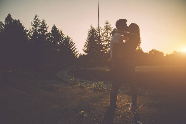 young couple kissing on a beautiful summer day in the sunset - love at first sight stock photos and pictures