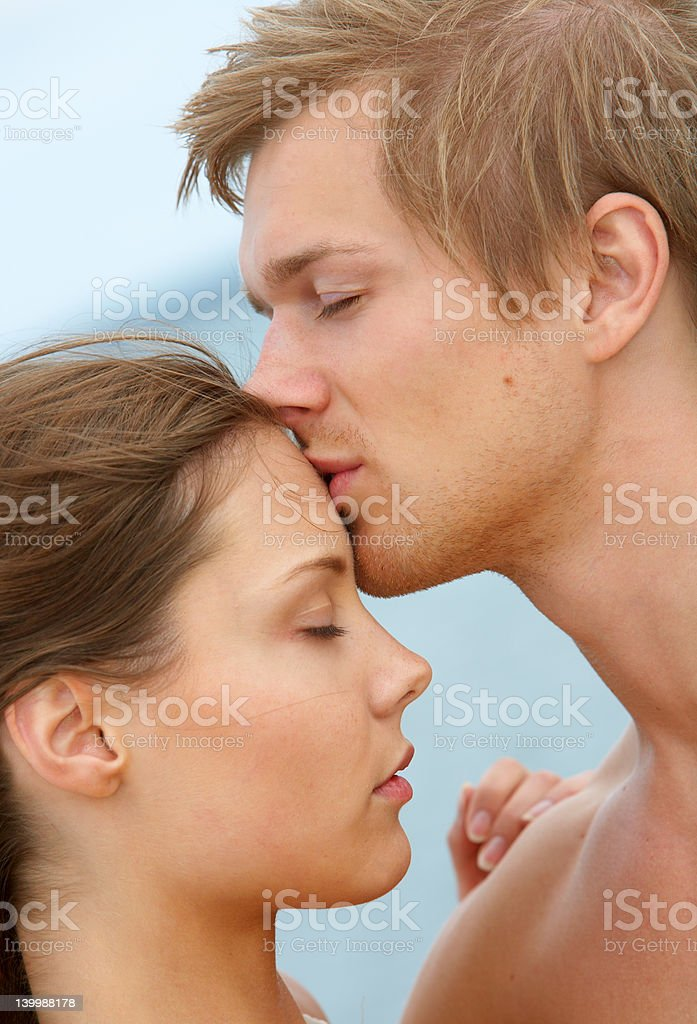 Young couple kissing on beach royalty-free stock photo
