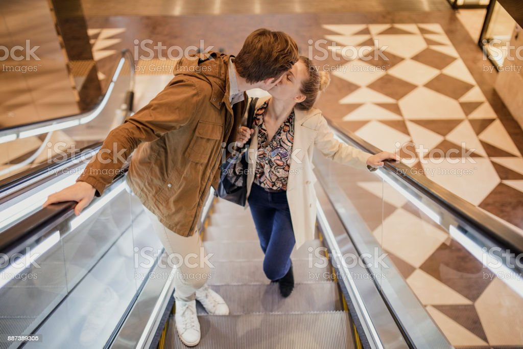 Young Couple Kissing on Escalator stock photo
