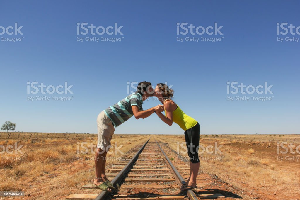 Young couple kissing on railroad in the desert stock photo