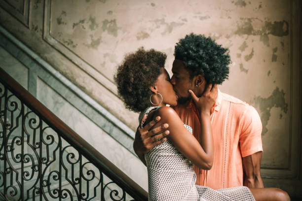 Young Couple kissing on steps against wall, Havana, Cuba stock photo