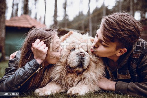 istock Young Couple Kissing The Chow Chow Dog on a Mountain Picnic 948171092