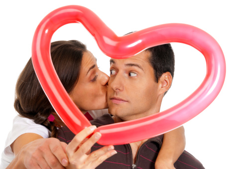 518335358 istock photo Young couple kissing through balloon heart surprise isolated 154221209